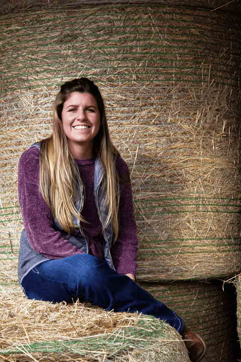 的Chanelle brusseau sits on hay bale by the U of I Beef Center.