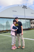 A mother and son st和 on the practice field of the ASUI-Kibbie Activity Center.